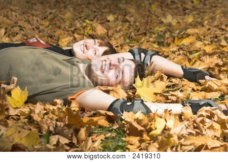 Couple Lies On Yellow Leaves