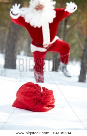 Santa Claus running to his sack lost in winter wood