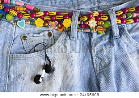 Close-up of worn blue jeans with headphones in the pocket and colorful belt of beads