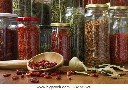 still life composition of many different spices teas and herbs on a wooden table