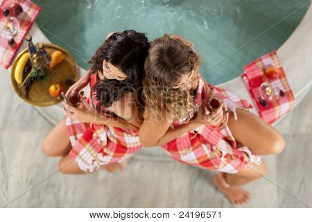 Wellness - two women, presumably they are friends, are relaxing in relaxation room with tea and fruits