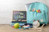 School Backpack With Coloured Pencil And Back To School Text On Blackboard On Wood Table Background. poster