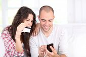 stock photo of mobile-phone  - Young couple doing online shopping with smartphone - JPG