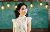 Woman With Long Hair In White Blouse Stands In Classroom. Lady Strict Teacher On Relaxed Face Stands poster