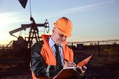stock photo of oil rig  - Oil worker in orange uniform and helmet on of background the pump jack and sunset sky - JPG
