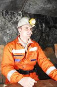 pic of gold mine  - Smiling miner in a mine shaft having a break stock photo - JPG