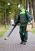 image of leaf-blower  - Landscaper operating gasoline Leaf Blower while cleaning the tracks in the park - JPG