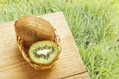 Fresh Ripe Kiwi Fruit On Wooden Table And On Green Grasses Background. Natural Organic Ripe Fruits.  poster