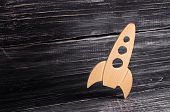 Wooden Space Rocket In Retro Style Is On A Dark Wooden Background. The Space Industry, The Developme poster