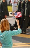 pic of waving american flag  - A girl waving an American flag during a parade - JPG