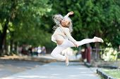 Happy Girl Jump High In Summer Park. Small Child Smile With Flying Hair In Motion Feeling Free. Fash poster