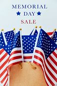 the text memorial day sale and a brown paper shopping bag with many flags of the United States poster