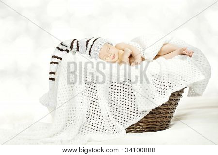 Sleeping Newborn Baby In Woolen Hat Lying In Basket With Blanket