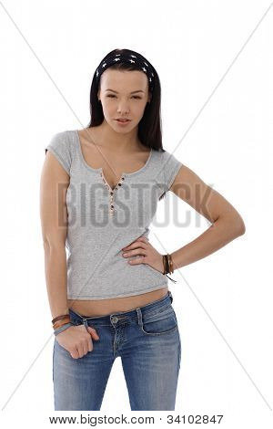 Young schoolgirl posing in jeans and t-shirt with hand on hip.