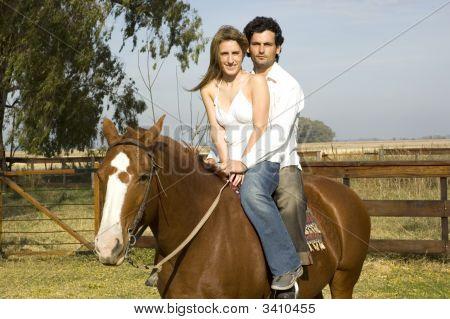 Young Couple Riding Their Horse