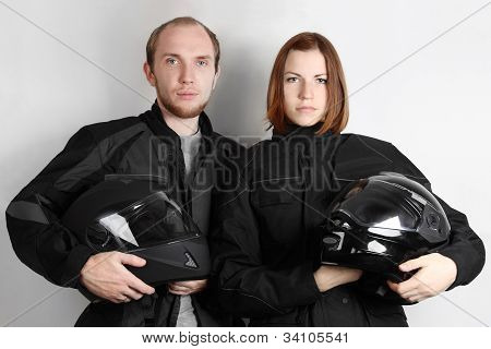 Young Motorcyclists Man And Woman Holding Helmets In Studio