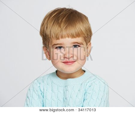 Smiling baby boy in blue pullover portrait