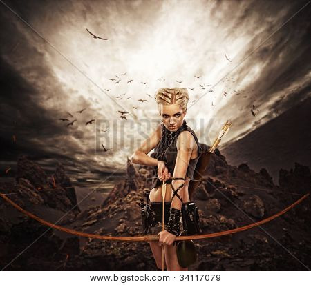 Woman archer against storm over rocks