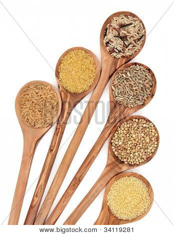 Healthy food of brown and wild rice, bulgur wheat, couscous, rye grain and  buckwheat grain in olive wood spoons over white background.