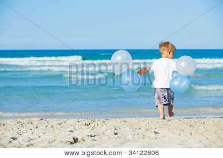 boy plays with ballons on the beach