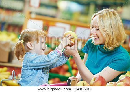 woman and little girl choosing apple during shopping at fruit vegetable supermarket