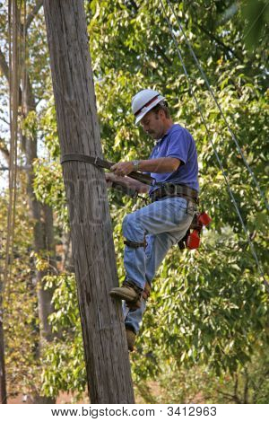 Utility Worker Climbing Pole