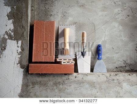 construction stainless steel trowel tools and bricks on cement mortar wall