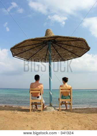 Couple Under Umbrella At The Beach