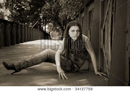 attractive girl sitting on bridge. outdoor shot
