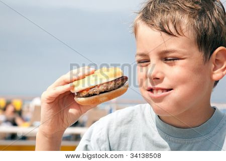 smiling hungry boy eating hamburger on ship