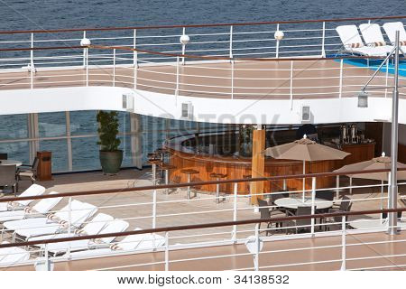 top floor of ship with deck chairs  bar view on sea
