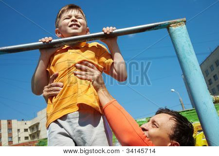 Kid doing chin-ups, his father helping him