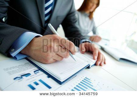 Pessoa de negócios irreconhecível analisando gráficos e tomar notas