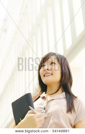 A young Asian woman looking far away to bright light in front of a modern office building, with diary on hand.