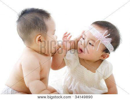 Two Asian babies having baby talk