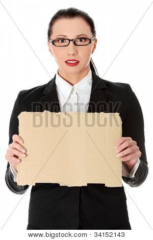 Young beautiful businesswoman is showing paper cardboard.  She's standing and wearing black suit and glasses. Isolated on the white background.