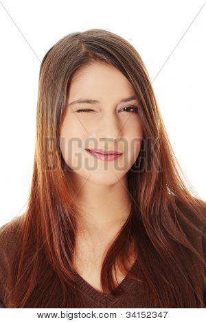 Young beautiful woman is smiling and winking. Long hair, brown sweater.