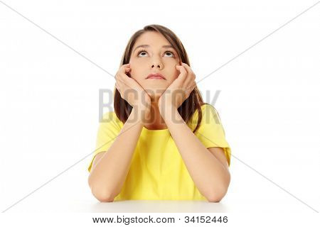 Student girl is sitting and looking up, dreaming or thinking with elbows on the table and chin based on the hands. Isolated on the white background.
