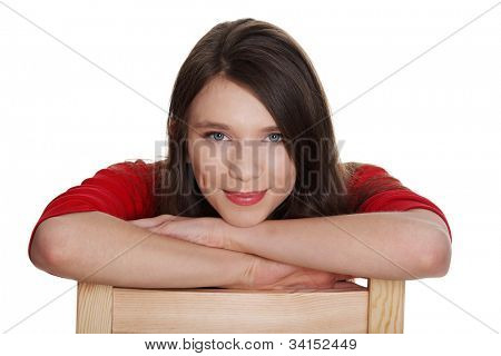 Young woma is sitting and smiling. She wears red blouse. She is based on the chair. Isolated on the white background.