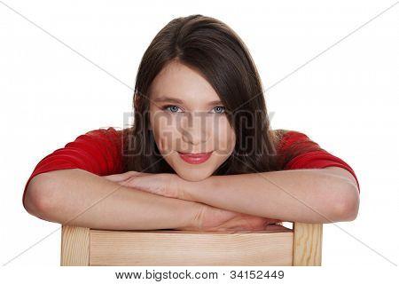 Woma jovem está sentado e sorrindo. Ela veste blusa vermelha. Ela baseia-se na cadeira. Isolado sobre o