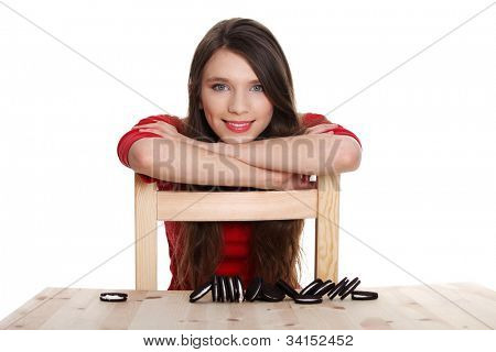 Young girl and cookies on the table. She is sitting with arms based on chair. Isolated on the white background.
