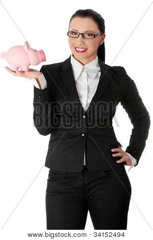 Young beautiful businesswoman is showing pink piggybank. She's standing and wearing black suit and glasses. Isolated on the white background.