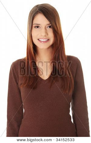 Young beautiful woman is looking straight and smiling. Long hair and brown sweater. Isolated on the white background.