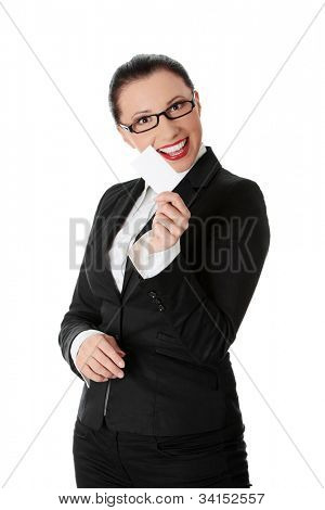 Young beautiful businesswoman is showing business card.  She's standing and wearing black suit and glasses. Isolated on the white background.