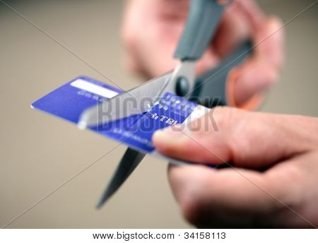 Hands cutting a credit card with scissors