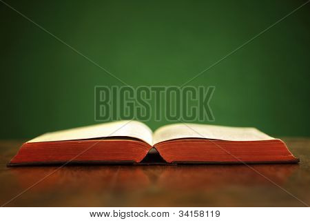 Bible on table with green background and copy space