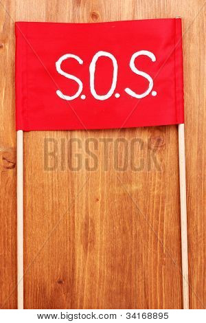 SOS signal written on red cloth on wooden background