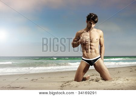 Sensual male model posing on beach with sand and ocean