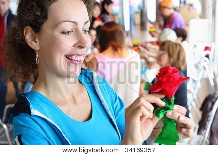 beautiful woman dressed in blue sports suit holds artificial red rose
