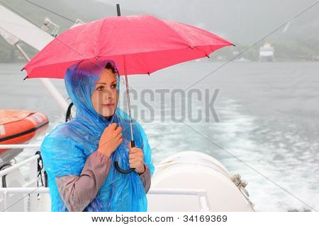 beautiful woman dressed in blue raincoat holds pink umbrella at small boat; it rain